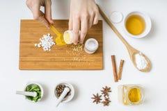 Sikt från överkant på händer som förbereder hemlagade skönhetsmedel från ingredienser Arkivbild