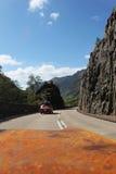 Sikt från bilen på vägen med en annan bil i skotsk Skotska högländerna royaltyfri foto