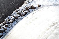 Sikt från bron till stenarna på bankerna av floden i vintern arkivfoto