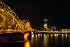 Sikt från Cologne till Deutz på flodRhen och den Hohenzollern drevbron på natten Royaltyfria Bilder