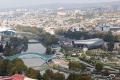 Sikt från den Narikala kullen av den nya Tbilisien, huset av rättvisa, bron av fred Arkivfoto