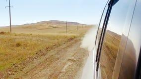 Sikt från den rörande bilen för fönster på den dammiga lantliga vägen med ökenfält och kullar
