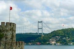 Sikt från den Rumeli Hisari fästningen till den Bosphorus bron och den asiatiska delen av Istanbul Turkiska flaggor på tornet och royaltyfri bild
