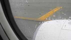 Sikt från det plana fönstret med regndroppar på flygplatslandningsbana och den plana motorn arkivfilmer