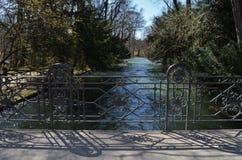 Sikt från en bro med den utmärkt tillverkade ledstången och den flödande floden och träd i bakgrunden arkivbild