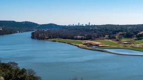 Sikt från en högväxt kulle av en flod nära sjön Travis med den synliga sikten av Austin horisont långt borta royaltyfria foton