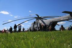 Sikt från ett fält för grönt gräs till en tungt transporthelikopter och folk mot en blå himmel arkivbild