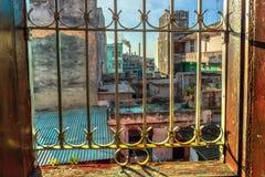 Sikt från ett fönster med openwork galler på gammalt, skrapat, dilapid arkivfoton