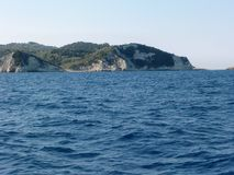 Sikt från ett fartyg på den steniga kusten av Antipaxos i Grekland royaltyfria foton