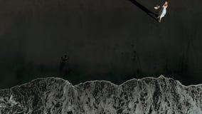 Sikt fr?n ett surr p? en flicka i en kl?nning p? stranden med svart sand i Los Gigantes, Tenerife, kanarief?gel?ar, Spanien arkivfilmer