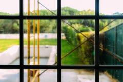 Sikt från fönster av den generiska trädgården som renoveras - selektiv fokus på fönster royaltyfria bilder