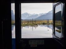 Sikt från fönster av drevet i Alaska med dammet, fältet och snowcapped berg bortom arkivbild