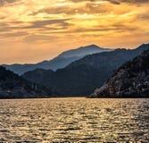Sikt från havet till den bergiga kusten med solnedgång Arkivbild