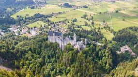 Sikt från luften till slotten av den Neuschwanstein slotten i de alpina bergen Arkivbild