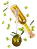 Sikt från ovannämnt av en olivolja i flaska, i en sked och en rå oli Royaltyfria Foton