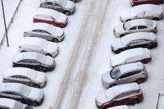 Sikt från ovannämnt på anseendet i linjer snö täckte bilar i andra sidan av den hala vägen, vinterparkeringsplats nära byggnad fotografering för bildbyråer