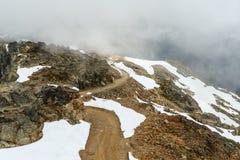 Sikt från ovannämnt på en landsväg, stenig väg som spolar i moen Royaltyfri Fotografi