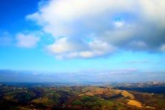 Sikt från ovannämnt på ett bergigt landskap under den blåa himlen med moln arkivfoton