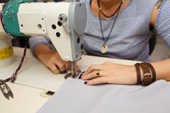 Sikt från ovannämnt på händer av den kvinnliga skräddaren som arbetar på symaskinen klänningtillverkningsbransch royaltyfri foto