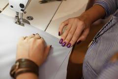 Sikt från ovannämnt på händer av den kvinnliga skräddaren som arbetar på symaskinen klänningtillverkningsbransch arkivfoto