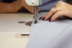 Sikt från ovannämnt på händer av den kvinnliga skräddaren som arbetar på symaskinen klänningtillverkningsbransch royaltyfri bild