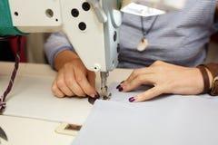 Sikt från ovannämnt på händer av den kvinnliga skräddaren som arbetar på symaskinen klänningtillverkningsbransch arkivfoton