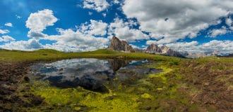 Sikt från passoen Giau som monterar Ra Gusela från Nuvolau gruppe och Tofana eller Le Tofane Gruppe med moln, berg som avspeglar  Arkivbilder