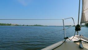 Sikt från pilbåge av att segla yachten ashore på en sommardag stock video