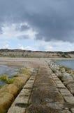 Sikt från pir som ska sättas på land, och klippor med blå himmel och stormiga moln Arkivfoton