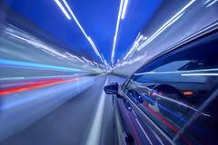Sikt från sida av bilinflyttningen en nattstad Arkivfoto