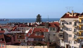 Sikt från sidan på taken av hus under de röda tegelplattorna mot den blåa himlen med vita moln och horisonten av havet arkivfoto