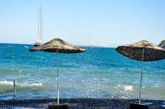 Sikt från stranden med två slags solskydd till det Aegean havet Royaltyfri Bild