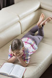 Sikt för hög vinkel av flickaläseboken, medan ligga på soffan hemma Royaltyfria Foton