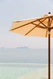 Sikt från oändlighetskantpöl med slags solskydd till havet Royaltyfri Bild