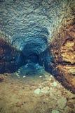 Sikt in i en tom medeltida katakomb Tunnelen som grävas i orange sandsten, vaggar Royaltyfria Bilder