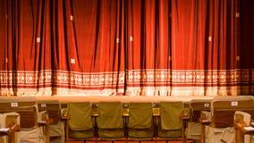Sikt inifrån en teater med etappstolar och den röda gardinen arkivbild