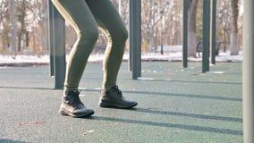 Sikt nedanför bältet utför den idrotts- flickan för ben det satta blocket för övningsgenomköraren i vintern på en solig dag arkivfilmer