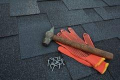Sikt på Asphalt Roofing Shingles Background Taksinglar - taklägga Asphalt Roofing Shingles Hammer handskar och spikar Royaltyfri Bild
