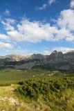 Sikt på berg i sommar och blå himmel med moln Arkivbild
