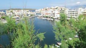 Sikt på cityscapen av Agios Nikolaos Crete Greece Fartyg på den lilla vulkansjövoulismenien och dess hamn houses traditionellt lager videofilmer
