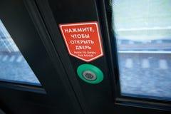 Sikt på dörrtryckknappen som ska göras för att låsa signalen för lokala dörrar som upp öppnar, medan drevet stoppar på en station arkivfoton