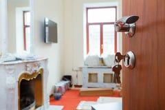 Sikt på den öppnade dörren med tangenter i låset och metalldörrhandtaget av lägenheten med spisen under under-renovering Fotografering för Bildbyråer