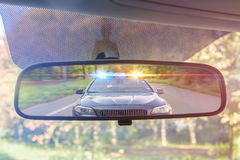Sikt på den bakre spegeln av en bil Polisbilen med ljus och siren jagar dig royaltyfri bild