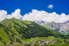 Sikt på den Gergeti Treenighetkyrkan - Tsminda Sameba, nära byn av Gergeti i Caucasian berg, Georgia arkivbild