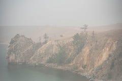 Sikt på den Olkhon ön under dimman baikal lake Royaltyfri Bild
