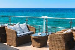 Sikt på en tom lyxig balkong nära havet med rottingmöblemang royaltyfri foto