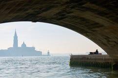 Sikt på en Venedig kyrka med två vänner under en bro Fotografering för Bildbyråer