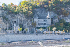 Sikt på grottakyrka i Budapest acros den Denube floden Arkivfoto