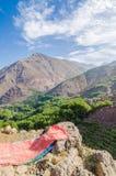 Sikt på härligt högt landskap för kartbokberg med den frodiga gröna dalen, steniga maxima och röd matta, Marocko, Afrika Arkivbilder