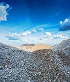 Sikt på högar av grått granitgrus och arkivbilder